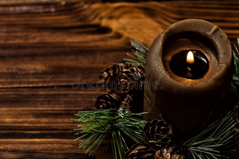 A lit brown candle is decorated with a spruce branch with small cones. Brown wooden boards on the background. royalty free stock photo
