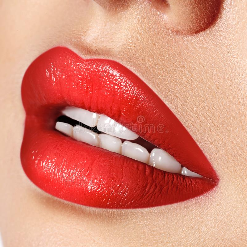 Close-up macro shot of female mouth. Glamour red lips Makeup with sensuality gesture. Red gloss lipstick stock photography