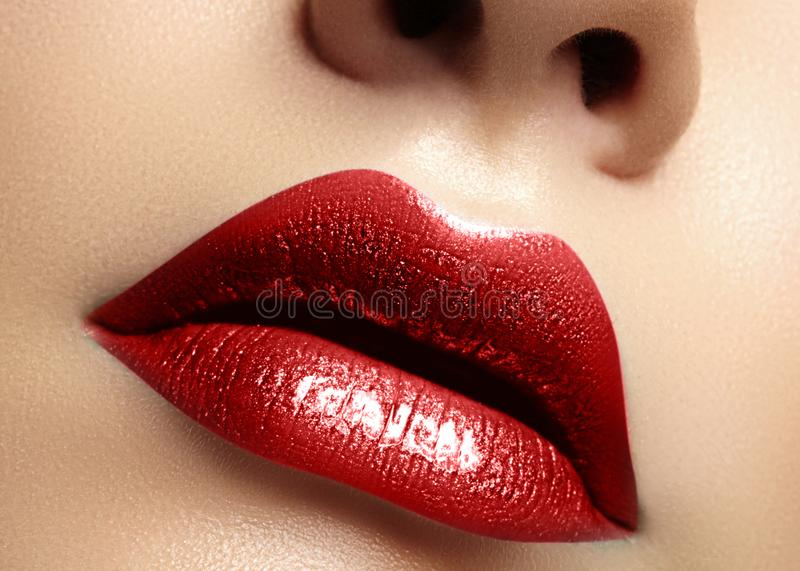 Close-up macro shot of female mouth. Glamour red lips Makeup with sensuality gesture. Metalic gloss lipstick stock photography
