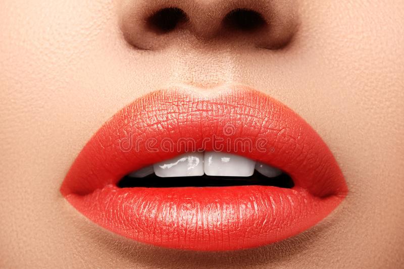 Close-up macro shot of female mouth. Glamour red lips Makeup with sensuality gesture. Orange colour. Full lips stock images