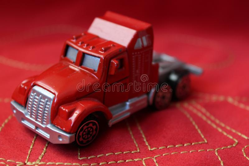 Close-up macro shot of a red toy truck on a red background. Close-up macro shot of a red toy truck on a red Textile material and golden stitching stock image