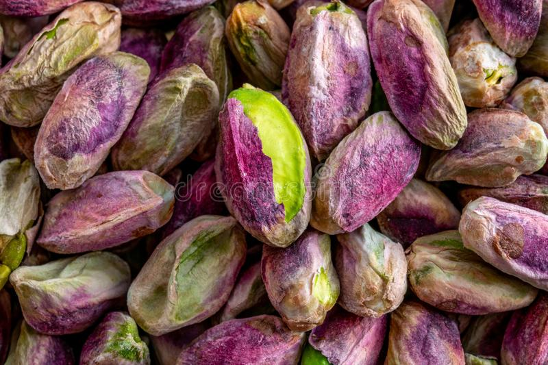 Close-up macro shot of roasted and shelled Australian pistachio nuts. These seeds have a mauve-colored skin and light green flesh and are widely considered to stock photography