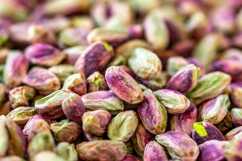 Close-up macro shot of roasted and shelled Australian pistachio nuts. These seeds have a mauve-colored skin and light green flesh and are widely considered to stock photo