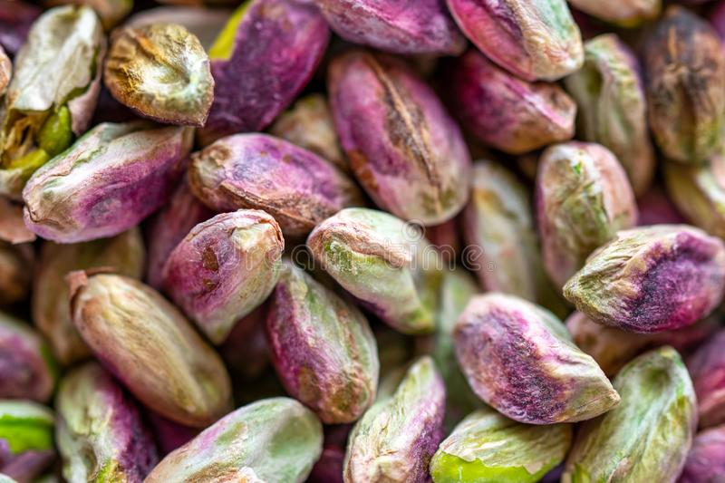 Close-up macro shot of roasted and shelled Australian pistachio nuts. These seeds have a mauve-colored skin and light green flesh and are widely considered to stock images