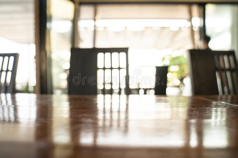 Close up and macro shot wood table surface with blur chair behind in silhouette theme. For any product floor and background royalty free stock photos