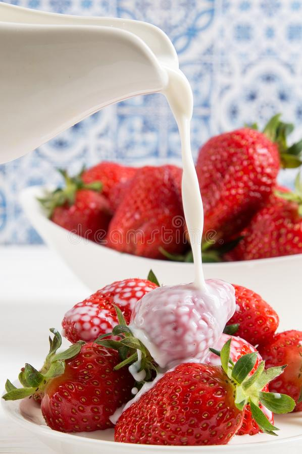 Close up, macro. Someone pours milk cream into a plate of delicious red strawberries. White wooden table, blue and white background royalty free stock photography