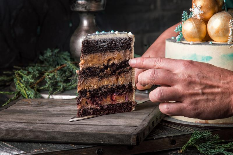 Close up, macro. Someone`s hands are serving a cut piece of New Year`s chocolate cake on a wooden board. Dark background stock photo