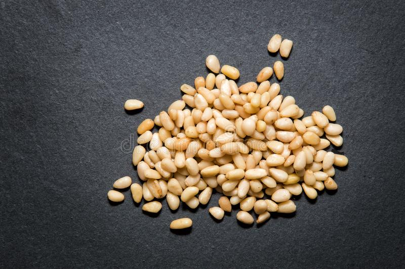 Close up. Top view. A handful of nutritious pine nuts on black background. Copy space stock photography