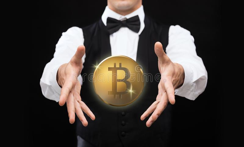 Close up of magician with bitcoin over black stock images