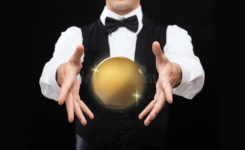 Close up of magician with golden coin over black royalty free stock image