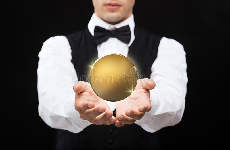 Close up of magician with golden coin over black stock image