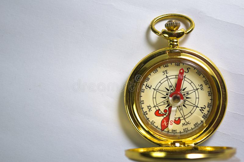 Close up magnetic golden compass isolated on white background stock photography