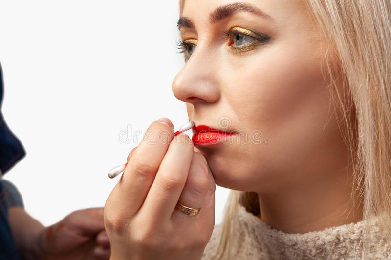 Close-up of the make-up of the lips of a model with a light-colored face, the make-up artist holds a cotton swab in his hands and stock image