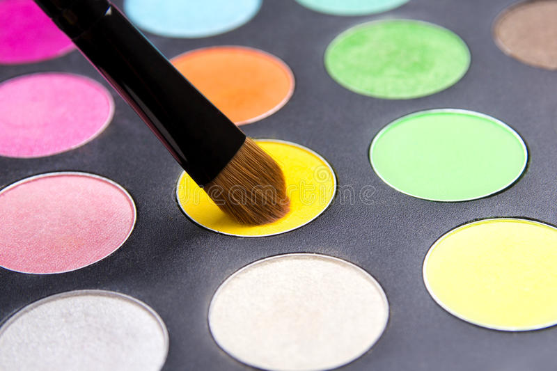 Close up of Make-up brush and colorful eyeshadow palette over bl. Ack background royalty free stock images