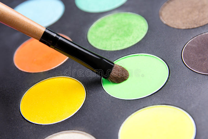 Close up of make-up brush and colorful eyeshadow palette. Over black stock image
