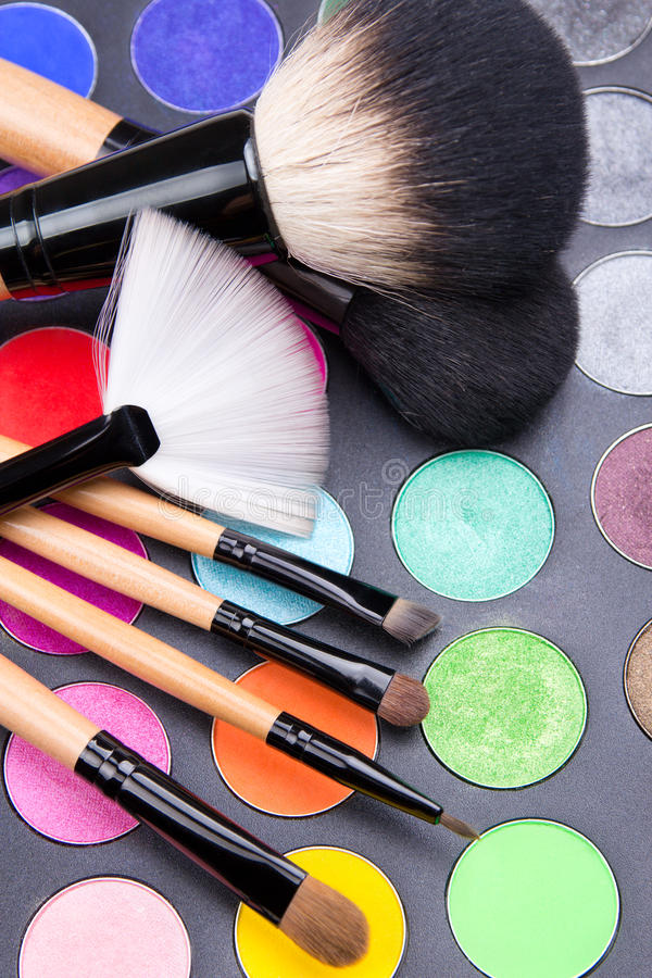 Close up of make-up brushes and colorful eyeshadow palette over. Black background stock photo