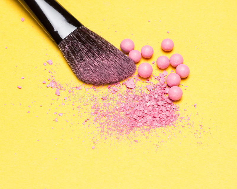 Close-up of makeup brush with crushed and whole shimmer blush ba. Lls pink color on yellow background stock images
