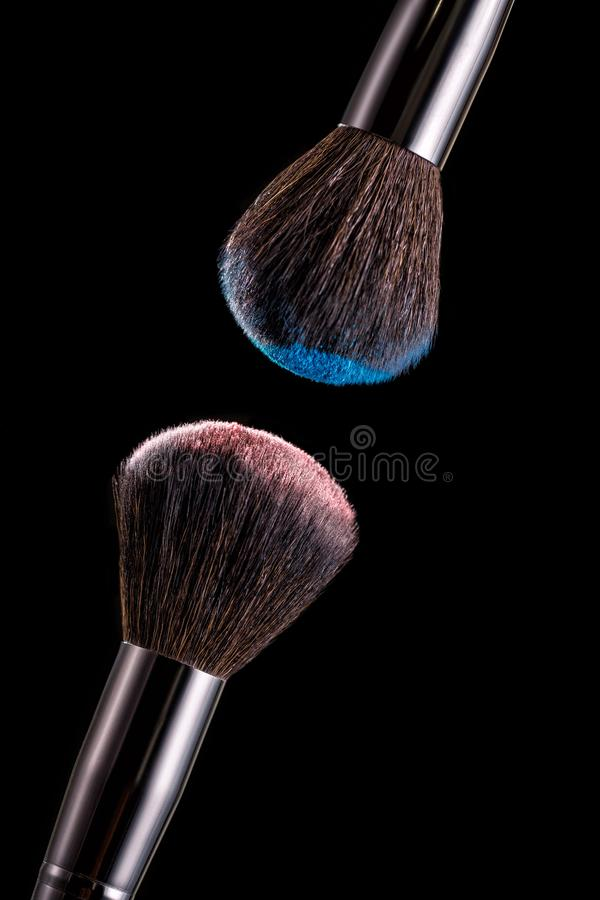 Makeup brush with powder on black background. Close-up of makeup brush with pink and blue eye shadow on black background royalty free stock photos