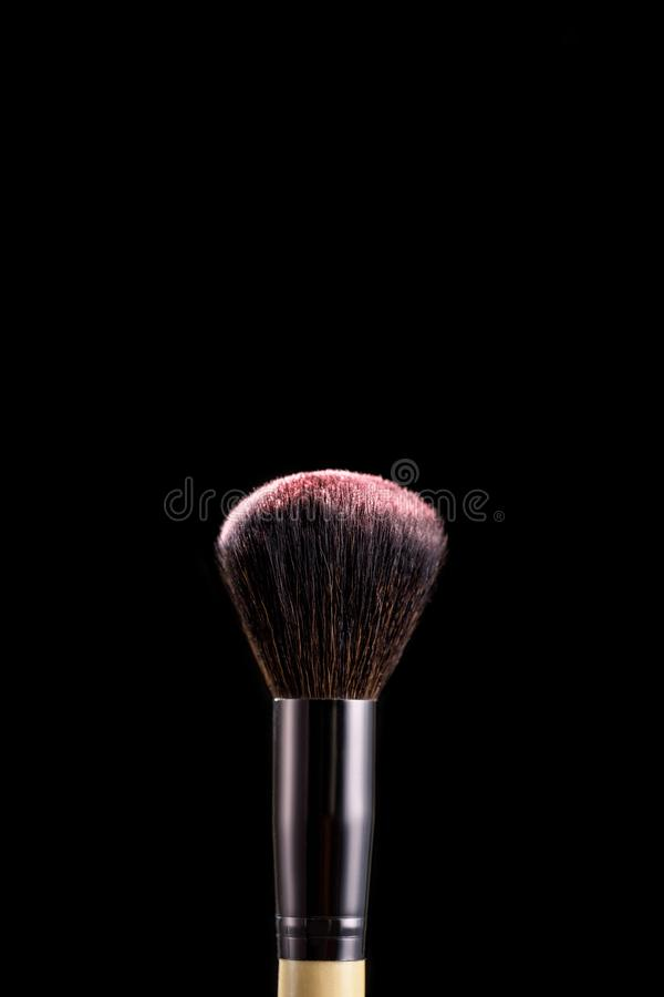 Makeup brush with powder on black background. Close-up of makeup brush with pink powder on black background stock photography