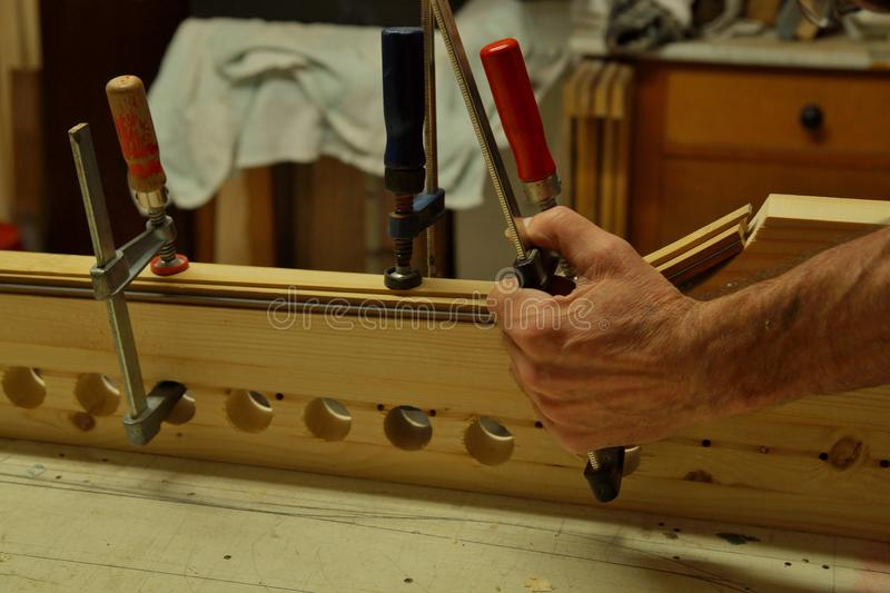 Close up of making recurved bow in workshop. male bow-maker royalty free stock photo