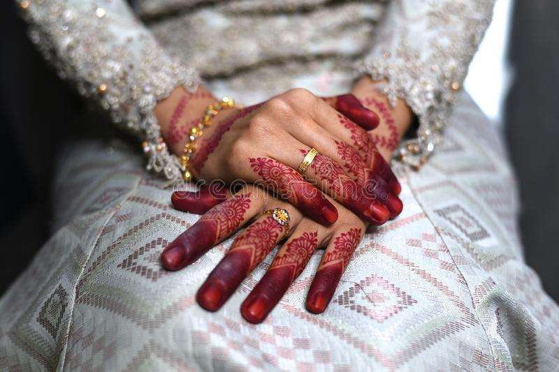 Close up of a malay bride hand with henna tattoo and gold rings her wedding day. Bride wearing songket fabric, malay tradition dress. Concept of tradition and royalty free stock images