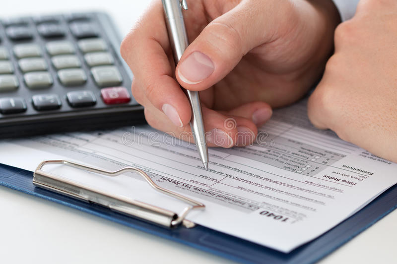 Close up of male accountant making calculations. Man writing something sitting at his office. Filling individual income tax return form 1040, making financial royalty free stock photography