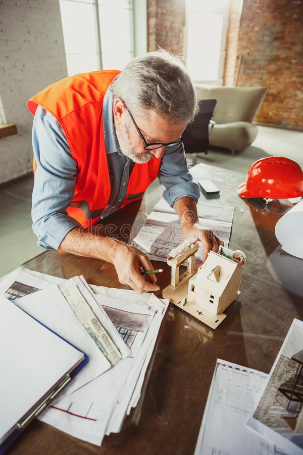 Close up of male architect-engineer making a model of house royalty free stock photos