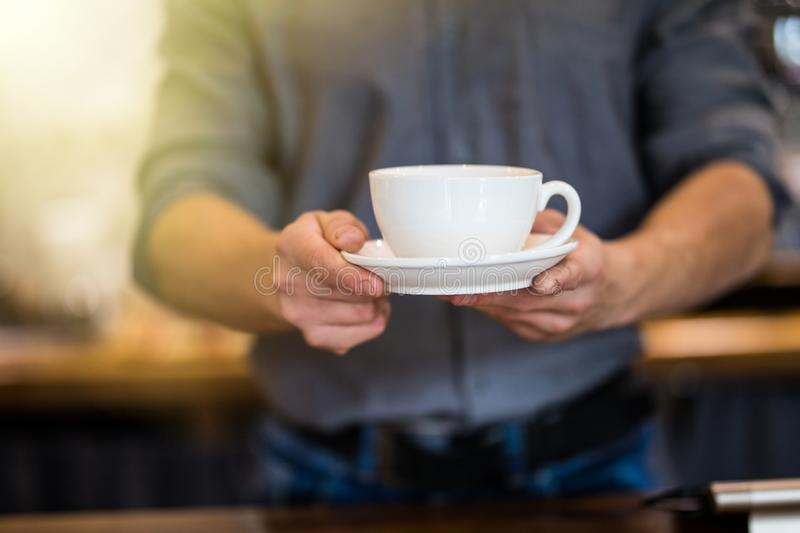 Close up of male barista serving cup of fresh coffee. Cup of coffee in the hands of waiter stock image