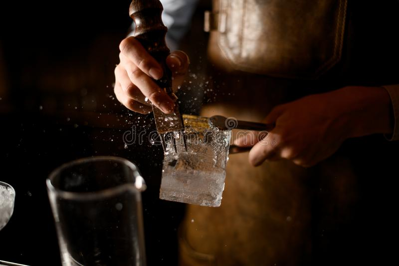 Close-up of bartender crushing the ice cube. Close-up of male bartender crushing the ice cube with ice crusher and tongs royalty free stock image