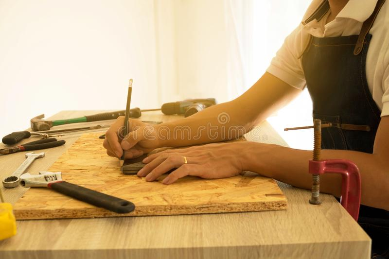 Close-up of male carpenter hands drawing mark on wooden flooring royalty free stock image