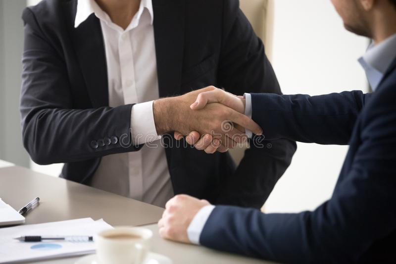 Close up of business partners shaking hands during meeting. Close up of male colleagues handshake making agreement or closing deal after meeting, business stock images