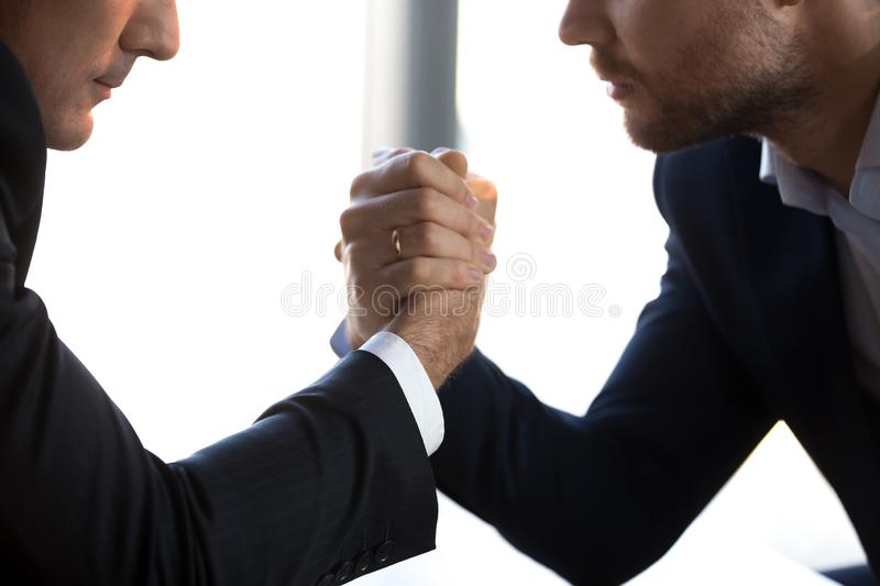 Close up of male competitors arm wrestle fighting at workplace. Close up of serious businessmen sit at table arm wrestling at workplace competing for leadership royalty free stock photography