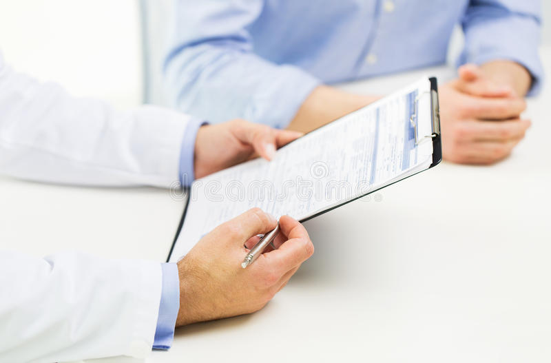 Close up of male doctor and patient with clipboard stock images