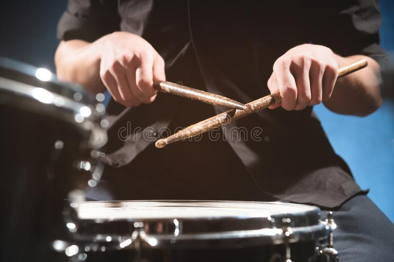 Close-up of a male drummer`s hand holding drum sticks while sitting behind a drum set.  royalty free stock image