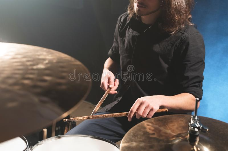 Close-up of a male drummer`s hand holding drum sticks while sitting behind a drum set.  royalty free stock photography