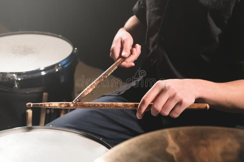 Close-up of a male drummer`s hand holding drum sticks while sitting behind a drum set.  royalty free stock images