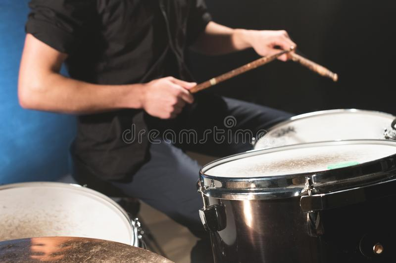 Close-up of a male drummer`s hand holding drum sticks while sitting behind a drum set.  stock photography