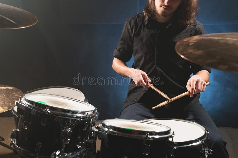 Close-up of a male drummer`s hand holding drum sticks while sitting behind a drum set.  stock photos