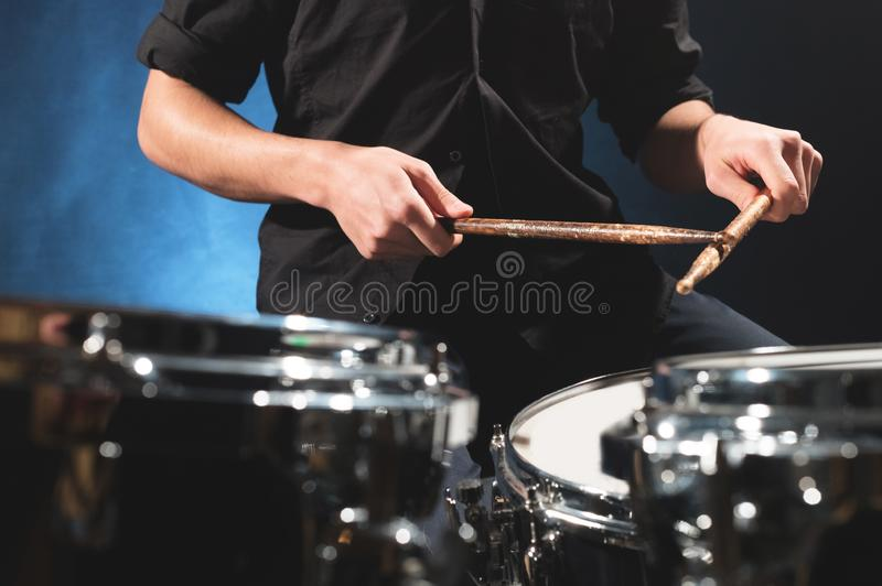 Close-up of a male drummer`s hand holding drum sticks while sitting behind a drum set.  royalty free stock photo
