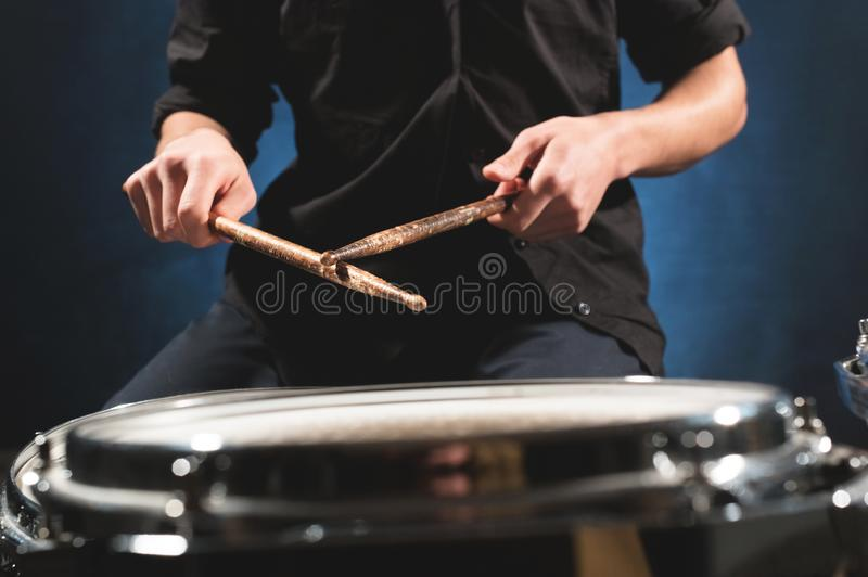 Close-up of a male drummer`s hand holding drum sticks while sitting behind a drum set.  stock image