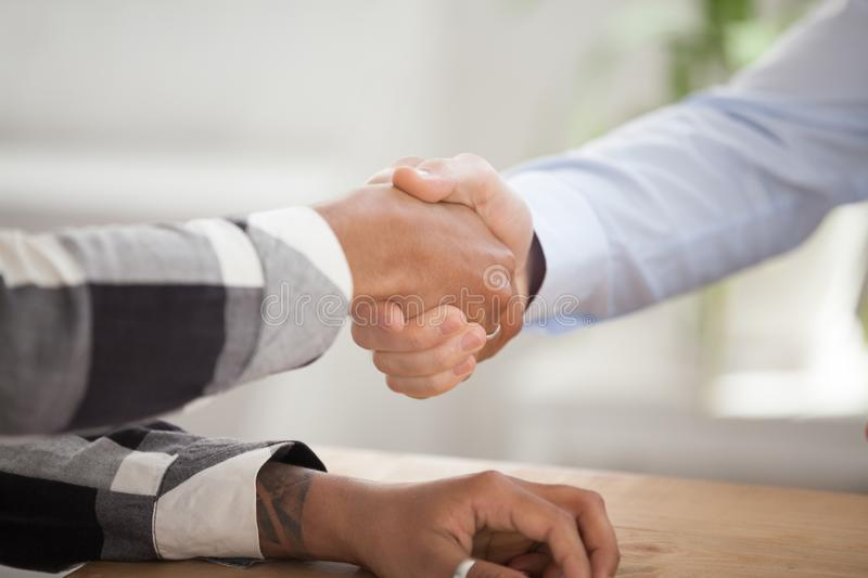 Close up of male employer handshake black candidate. Close up of male employer or businessman shake hand of black applicant thanking for interview, HR manager royalty free stock images