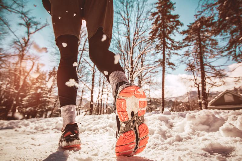 Close up of male feet running along winter road stock photo