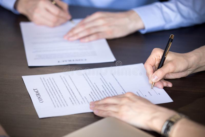 Close up of male and female hands signing two contracts stock photos
