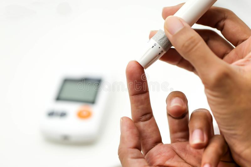 Close up of male finger with blood drop and test stripe to check stock photo