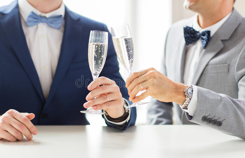 Close up of male gay couple with champagne glasses. People, celebration, homosexuality, same-sex marriage and love concept - close up of happy married male gay royalty free stock image