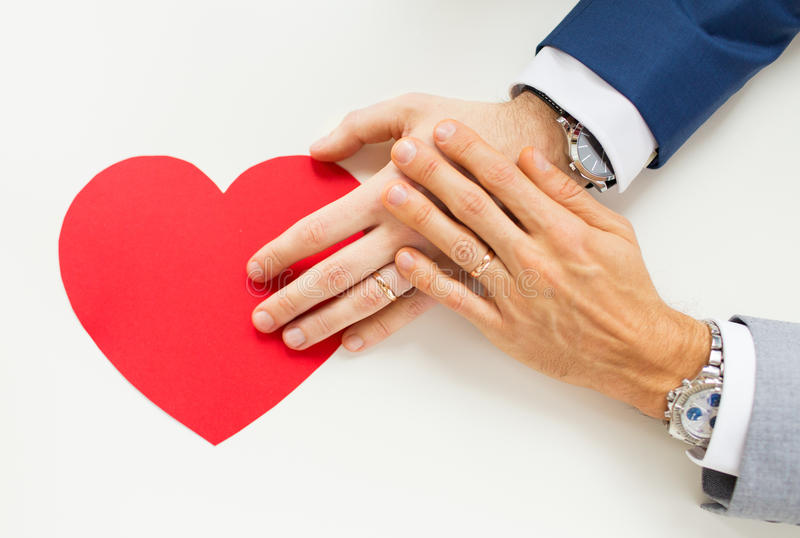 Close up of male gay couple hands with red heart. People, homosexuality, same-sex marriage, valentines day and love concept - close up of happy married male gay royalty free stock image