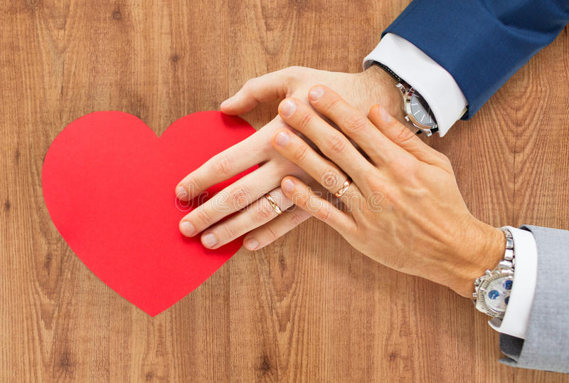 Close up of male gay couple hands with red heart. People, homosexuality, same-sex marriage, valentines day and love concept - close up of happy married male gay royalty free stock photo