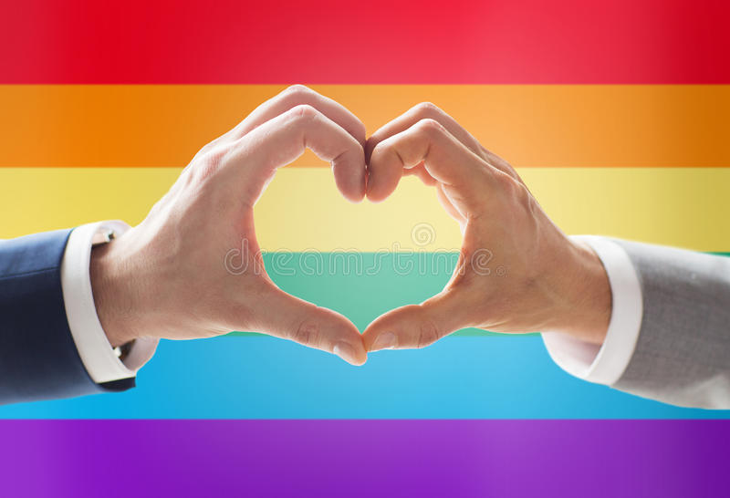 Close up of male gay couple hands showing heart. People, homosexuality, same-sex marriage, gesture and love concept - close up of happy male gay couple hands stock photos