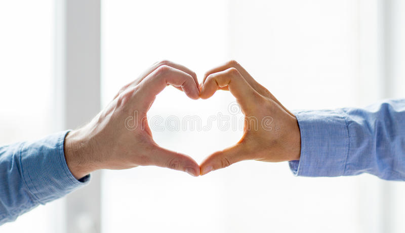 Close up of male gay couple hands showing heart stock image