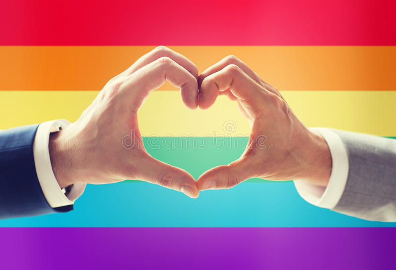 Close up of male gay couple hands showing heart. People, homosexuality, same-sex marriage, gesture and love concept - close up of happy male gay couple hands stock images